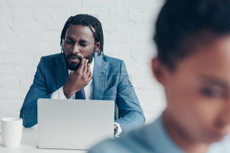 Photo pour Malheureux homme d'affaires afro-américain souffrant de douleurs dentaires alors qu'il était assis au bureau près d'un joli collègue - image libre de droit