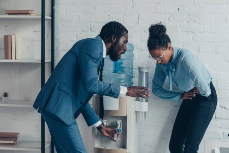 Photo for Worried african american manager giving glass of water to pretty colleague suffering from abdominal pain - Royalty Free Image