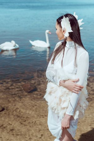 Photo pour Femme brune dans le costume blanc de cygne restant près de l'étang, regardant des oiseaux - image libre de droit
