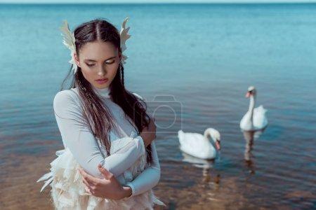 Photo pour Femme tendre dans les yeux de fermeture blancs de costume de cygne, restant près de la rivière avec des oiseaux - image libre de droit
