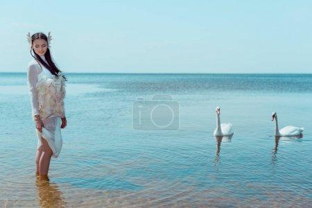 Photo pour Femme adulte dans le costume blanc de cygne restant dans la rivière près des oiseaux - image libre de droit