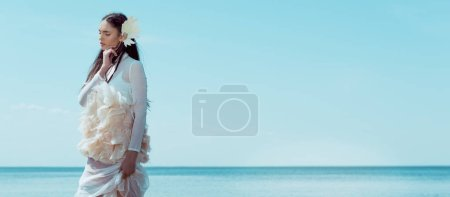 Photo pour Vue panoramique de belle femme en costume de cygne blanc debout sur fond de rivière et de ciel - image libre de droit