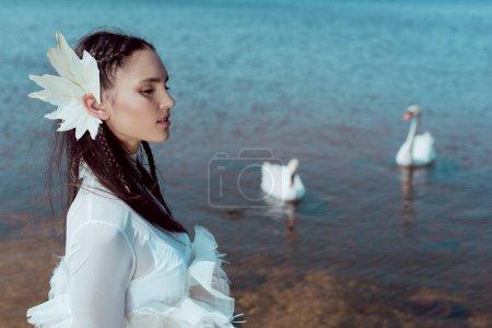 Photo pour Vue latérale de la femme tendre dans le costume blanc de cygne regardant loin, restant sur le fond avec des oiseaux et la rivière - image libre de droit