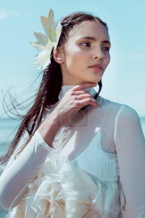 Photo pour Portrait of beautiful woman in white swan costume looking away - image libre de droit