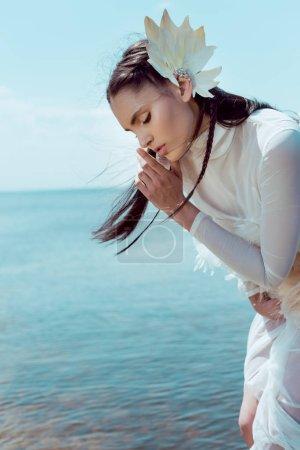 Photo pour Femme brune dans le doigt blanc de fixation de costume de cygne près des lèvres, faisant le signe de shh - image libre de droit
