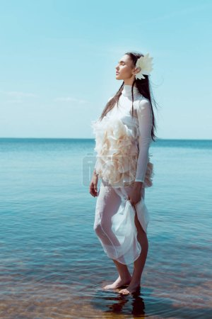 Photo pour Young woman in white swan costume standing on river and sky background, closing eyes - image libre de droit