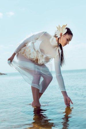 Photo pour Femme élégante dans le costume blanc de cygne touchant la rivière, regardant l'eau - image libre de droit