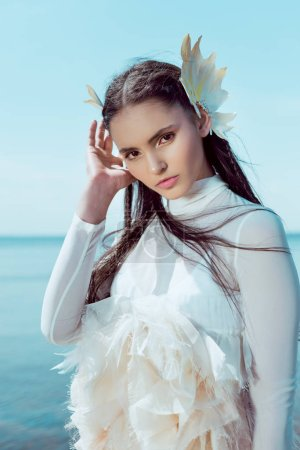 Photo for Portrait of tender woman in white swan costume looking at camera - Royalty Free Image