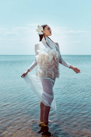 Photo for Dreamy and elegant woman in white swan costume standing on river backgrond - Royalty Free Image
