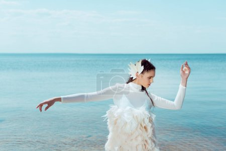 Photo pour Belle femme dans le costume blanc de cygne regardant loin, posant sur le fond de fleuve - image libre de droit