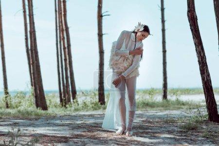 Photo pour Belle femme dans le costume blanc de cygne restant sur la plage sablonneuse près des arbres - image libre de droit