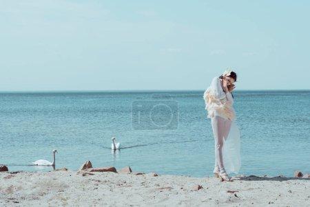 Photo pour Femme élégante dans le costume blanc de cygne restant près des oiseaux sur le fleuve bleu et le fond de ciel - image libre de droit