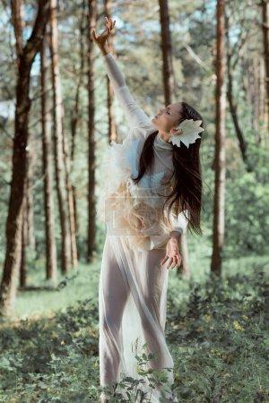 Photo pour Belle femme en costume de cygne blanc debout dans la forêt, les yeux fermés - image libre de droit
