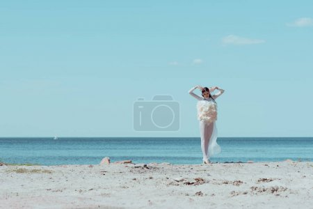 Photo pour Elegant woman in white swan costume standing on blue river and sky background - image libre de droit
