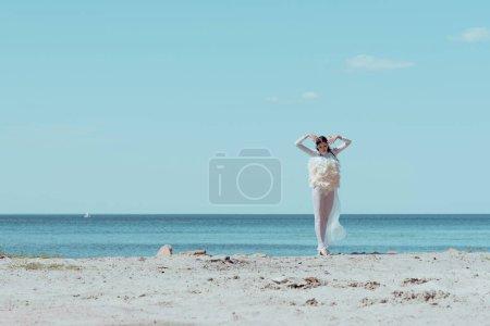 Photo pour Femme élégante dans le costume blanc de cygne restant sur le fleuve bleu et le fond de ciel - image libre de droit
