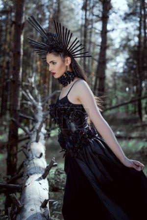 Photo pour Femme de brunette dans le costume de sorcière restant sur le fond de forêt - image libre de droit