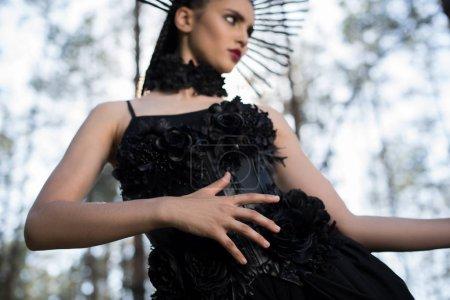 Foto de Vista de ángulo bajo de la mujer elegante en traje de bruja de pie en el bosque y el fondo del cielo, mirando hacia otro lado - Imagen libre de derechos