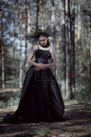 Elegante Frau im Hexenkostüm steht auf Waldboden und blickt in die Kamera