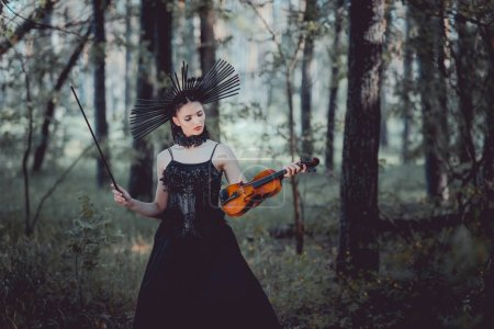 Elegante Frau im Hexenkostüm steht auf Waldboden und blickt auf Geige