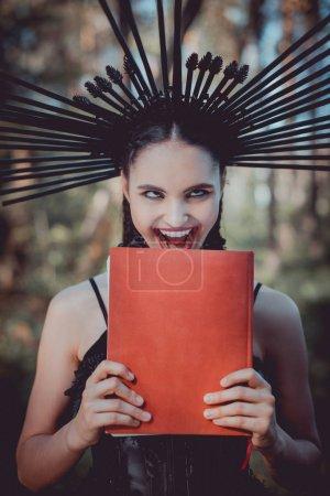 Foto de Mujer loca en traje de bruja negro con la corona en la cabeza mueca, sosteniendo libro rojo - Imagen libre de derechos
