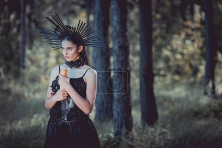 beautiful woman in witch costume standing on forest background, looking away, holding scroll