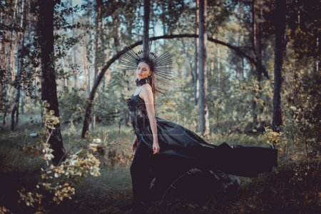 Photo pour Beautiful woman in witch costume standing on forest background - image libre de droit