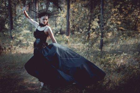Photo pour Femme de brunette dans le costume de sorcière avec la couronne sur la tête restant sur le fond de forêt - image libre de droit
