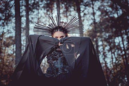 Foto de Low angle view of woman in witch costume with crown on head covering face black textile - Imagen libre de derechos