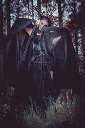 Foto de Mujer morena en traje de bruja y corona en la cabeza sosteniendo las manos con textil negro cerca de la cara, mirando hacia otro lado - Imagen libre de derechos
