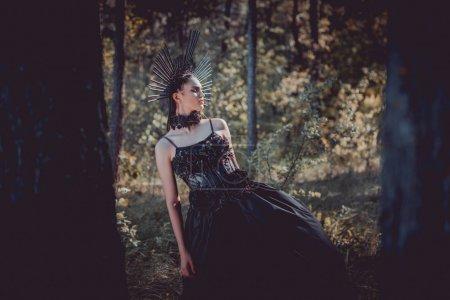 Photo pour Foyer sélectif de la belle femme dans le costume noir de sorcière restant entre les arbres - image libre de droit
