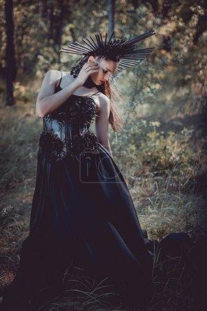 Foto de Mujer adulta en traje de bruja negro de pie en el fondo del bosque, mirando hacia otro lado - Imagen libre de derechos