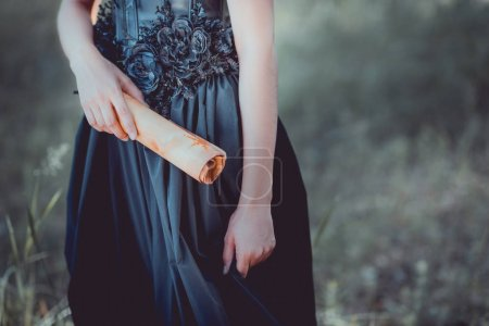 cropped view of woman in black witch costume standing with scroll in hand