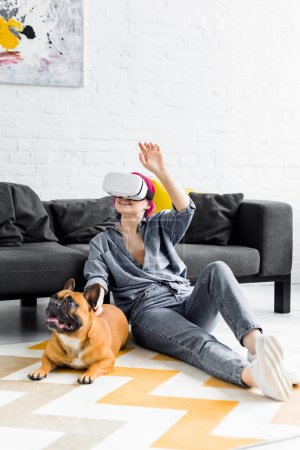 girl with colorful hair and VR headset sitting on floor near dog