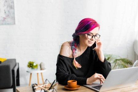 Photo pour Fille hipster avec des cheveux colorés assis derrière la table, en utilisant un ordinateur portable et parler sur smartphone - image libre de droit