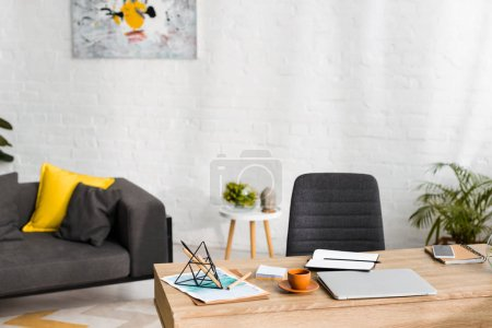 wooden table with notebooks, laptop and cup of coffee in living room with sofa