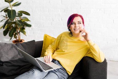 Photo pour Jolie fille avec des cheveux colorés assis sur le canapé, en utilisant un ordinateur portable tout en parlant sur smartphone - image libre de droit