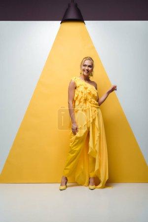 Photo pour Heureuse fille blonde souriant tout en posant et en faisant des gestes sur blanc et jaune - image libre de droit