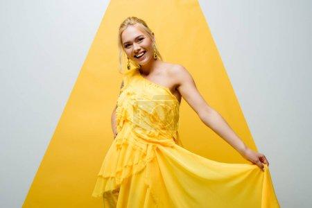 Photo pour Heureuse fille blonde souriant tout en posant et en regardant la caméra sur blanc et jaune - image libre de droit