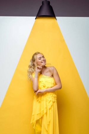 Photo for Happy young woman with closed eyes smiling on white and yellow - Royalty Free Image