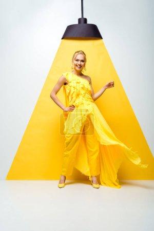 Photo pour Heureuse jeune femme debout avec la main sur la hanche et geste sur blanc et jaune - image libre de droit