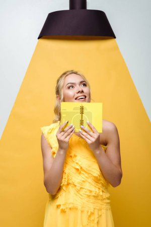 positive woman holding notebook while posing on white and yellow