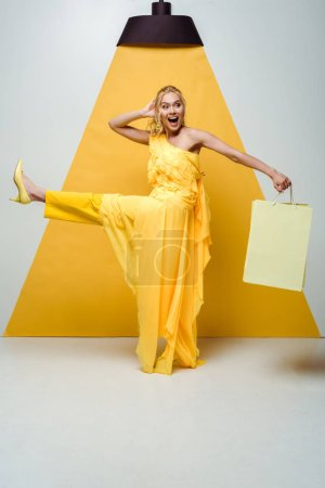 Photo for Happy blonde woman holding shopping bag while posing on white and yellow - Royalty Free Image