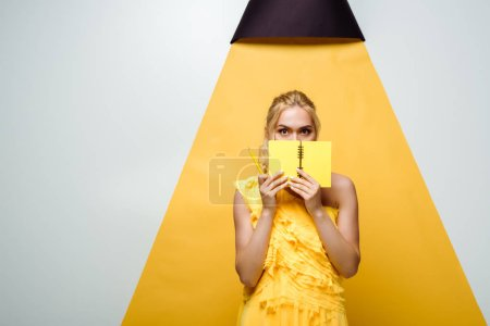 Photo for Young blonde woman covering face with notebook on white and yellow - Royalty Free Image