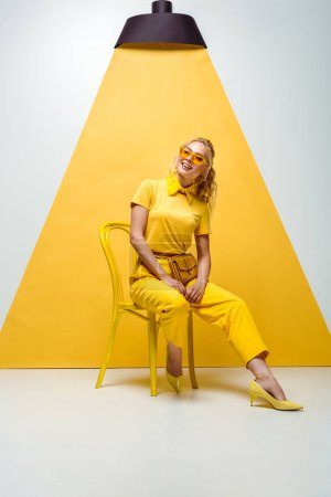 positive blonde woman in sunglasses sitting on chair on white and yellow