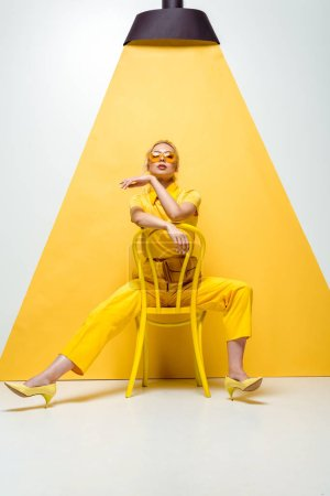 Photo for Attractive blonde woman in sunglasses sitting on chair on white and yellow - Royalty Free Image