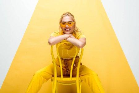 Photo pour Femme blonde gaie dans les lunettes de soleil assis sur la chaise sur blanc et jaune - image libre de droit