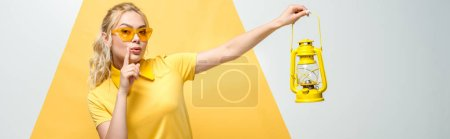 Photo for Panoramic shot of attractive blonde woman in sunglasses gesturing and holding vintage lamp on white and yellow - Royalty Free Image