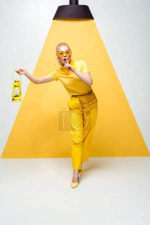 Photo pour Femme blonde en lunettes de soleil posant et montrant signe de silence tout en tenant lampe vintage sur blanc et jaune - image libre de droit
