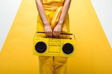 Photo pour Vue recadrée de femme posant avec la boombox rétro sur le blanc et le jaune - image libre de droit