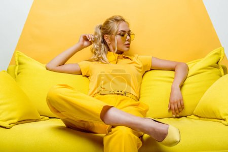 Photo for Attractive blonde woman sitting on sofa and touching hair on white and yellow - Royalty Free Image